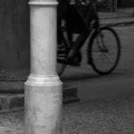 """Il Fittone """"IO ETERNO DURO!!""""  Fino al 1870 via Spaderie (oggi non più esistente), che collegava la piccola via Rizzoli dell'epoca con l'attuale via degli Orefici, era conosciuta per il tubo in gomma della famosa tabaccheria all'angolo, dal quale fuoriusciva una fiammella sempre accesa dove accendersi i propri sigari senza l'uso dei fiammiferi. Dopo che vi fu posto come paracarro un fittone, la cui forma ricordava un simbolo fallico, via Spaderie divenne il luogo di ritrovo dei Goliardi bolognesi, i quali eressero il fittone a loro mitico simbolo.  Mal visto dalla curia, dalla politica e dalla borghesia, in occasione dei lavori di ampliamento di via Rizzoli del 1912, lo si fece sparire in tutta fretta. L'evento provocò una rivolta studentesca culminata nell'occupazione del municipio e conclusasi il 13 maggio, quando il fittone fu portato su una barella da due pompieri in via Zamboni e collocato all'inizio del portico di Palazzo Poggi. Gli studenti festeggiarono il lieto fine sventolando bandiere mentre la banda suonava musiche goliardiche.  Il fittone subì varie traversie: scampò ad un tentativo di ratto da parte dei padovani nel 1912; fu spezzato durante il ratto modenese del 1947; fu ingabbiato da solido acciaio nel 1950; fu decapitato dai fiorentini nel 1958 e, nello stesso anno, fu uccellato (preso in pegno) dai ferraresi e trasferito all'interno dell'Università. Oggi l'originale è preziosamente custodito nella stanza dei goliardi presso il Museo Europeo degli Studenti di Palazzo Poggi."""